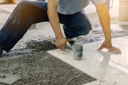 Workers use tile work equipment, renovation - handyman laying ti