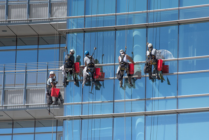 Group of window cleaners suspended from cables